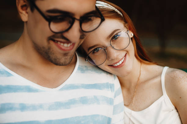 Close up portrait of a young couple sitting closely while smiling. Red haired girl with freckles looking at camera while leaning head on her boyfriend. stock photo