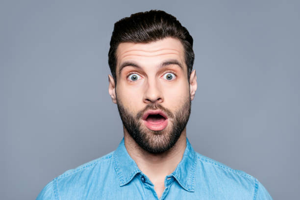 a close up portrait of a young surprised man with opened mouth isolated on gray background - sorpresa foto e immagini stock