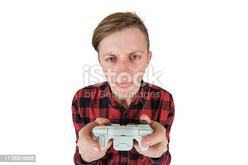 istock Close up portrait of addicted teenage boy has problems due to video games addiction, looking confused to camera, holding joystick console don't stop playing isolated over white. 1178924988