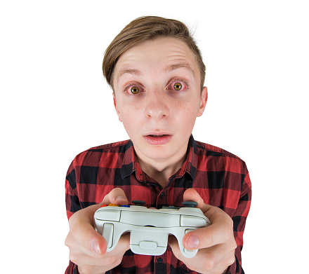 istock Close up portrait of addicted teenage boy has problems due to video games addiction, looking attentive with his bloody, red eyes, holding joystick console dont stop playing isolated over white. 1178926373