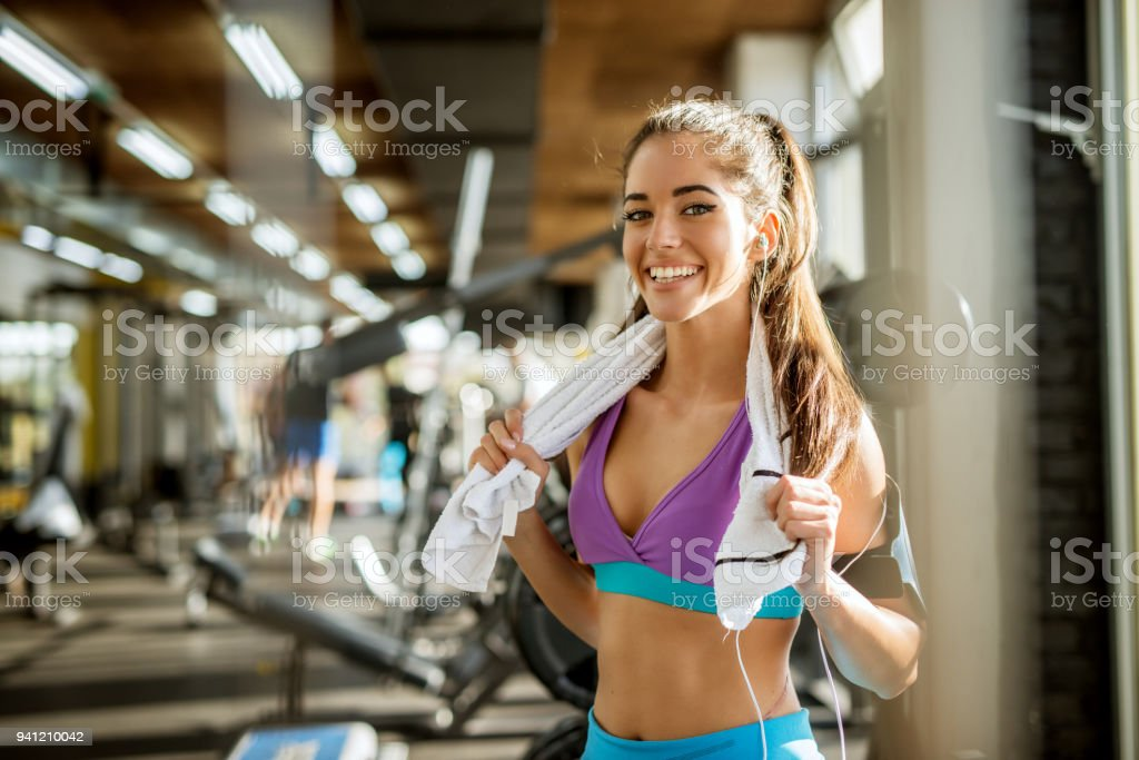 Close up portrait of adorable charming smiling young shape fitness girl with earphones holding a towel and posing while looking at the camera in the gym near the window. stock photo