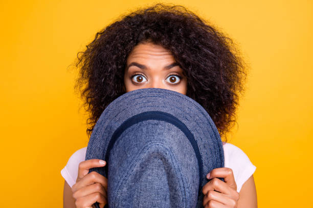 close up portrait of afraid scared girl hiding half face with hat looking with wide open eyes isolated on yellow background. tour trip vacation journey weekend concept - donna si nasconde foto e immagini stock