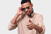 istock Close up portrait of African American young man with headphones listen the music and dancing. Happy smiling Afro male DJ wearing mirror sunglasses and casual outfit, posing over white studio wall. 1134195179