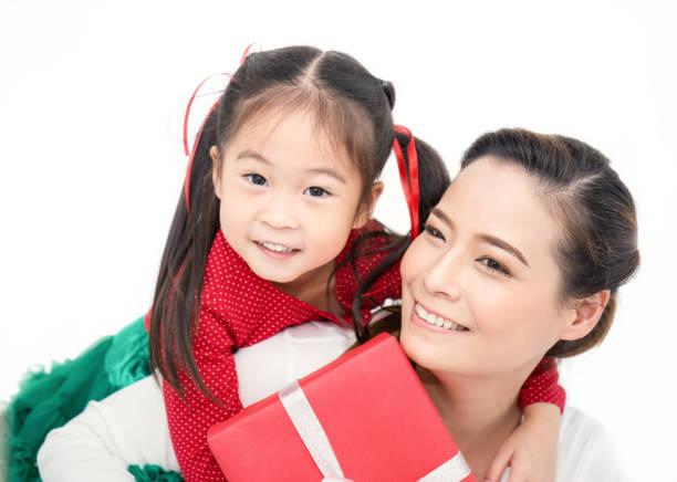 アジアの小さな幼児の女の子のクローズアップ肖像画は、白い背景に隔離されたギフトボックスで彼女の母親を驚かえます。ボクシングの日の休日の誕生日のクリスマスと母の日の概念。 ストックフォト