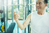 Close up portrait of asian senior man, thirsty asian senior man drinking a glass of water, refresh after workout