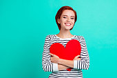 istock Close up portrait of attractive beautiful she her lady holding large bright red paper heart close to chest tight hug in love with whole world wearing white striped sweater isolated on teal background 1097744296