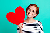 istock Close up portrait of attractive foxy beautiful she her lady holding large red paper heart in one hand suit to fire red short hairstyle hairdo in white striped sweater isolated on teal background 1097741654