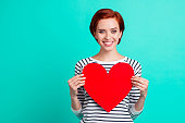 istock Close up portrait of attractive foxy beautiful she her lady holding large bright red paper card heart wish to share love with everybody wearing white striped sweater isolated on teal background 1097747084