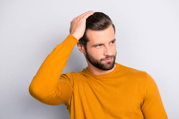 Close up portrait of attractive handsome virile masculine brutal guy combing back his long brown-haired furfur looking aside wearing color of mustard tight pullover isolated on gray background Close up portrait of attractive handsome virile masculine brutal guy combing back his long brown-haired furfur looking aside wearing color of mustard tight pullover isolated on gray background hair stubble stock pictures, royalty-free photos & images