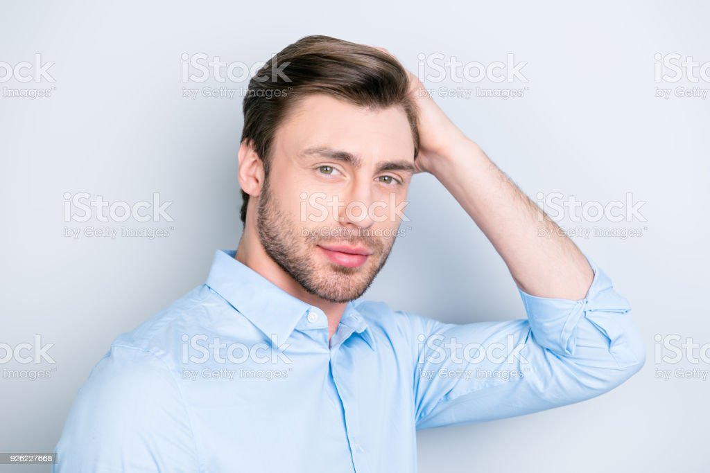 Close up portrait of attractive man touching his perfect hair and looking to the camera while standing over grey background stock photo