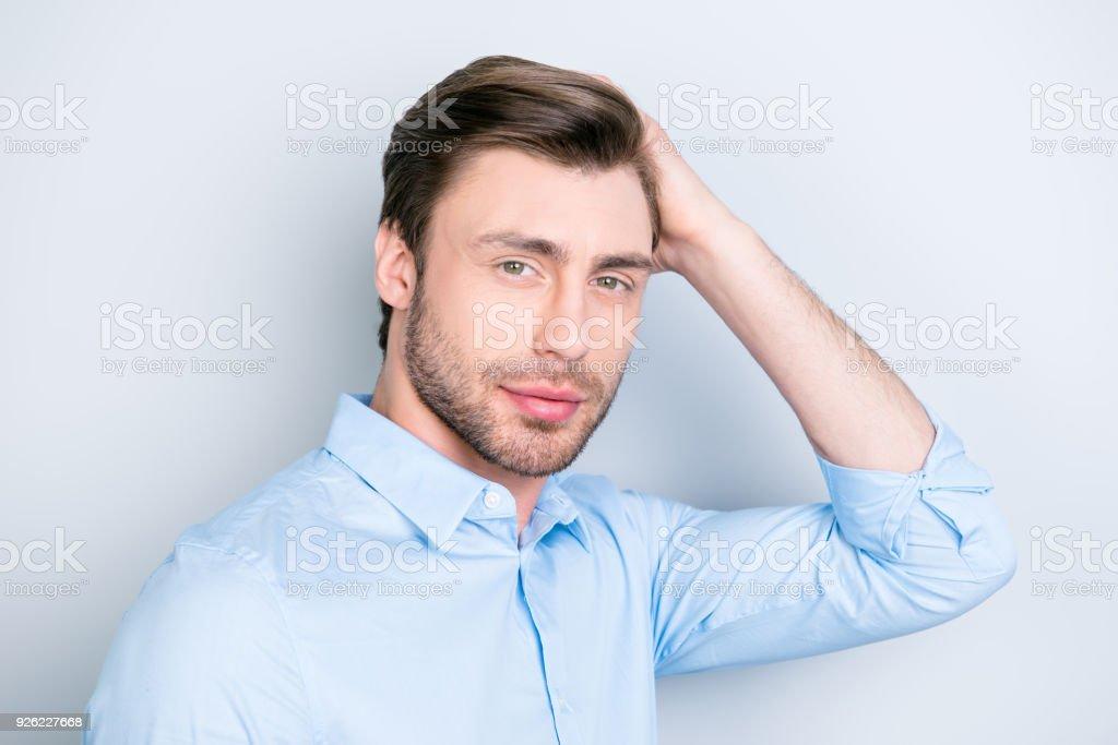 Primer plano retrato de hombre atractivo tocando su cabello perfecto y mirando a la cámara mientras está parado sobre fondo gris - foto de stock