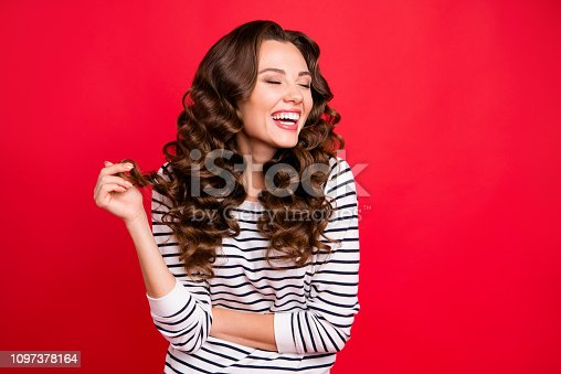 istock Close up portrait of attractive pretty cheerful she her girl mouth open gladly laughing with funny joke with one curl in hand white striped pullover isolated on red vivid background 1097378164