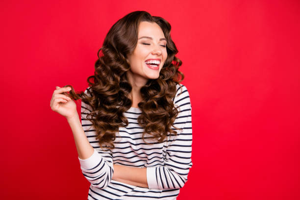 close up portrait of attractive pretty cheerful she her girl mouth open gladly laughing with funny joke with one curl in hand white striped pullover isolated on red vivid background - smile woman open mouth foto e immagini stock