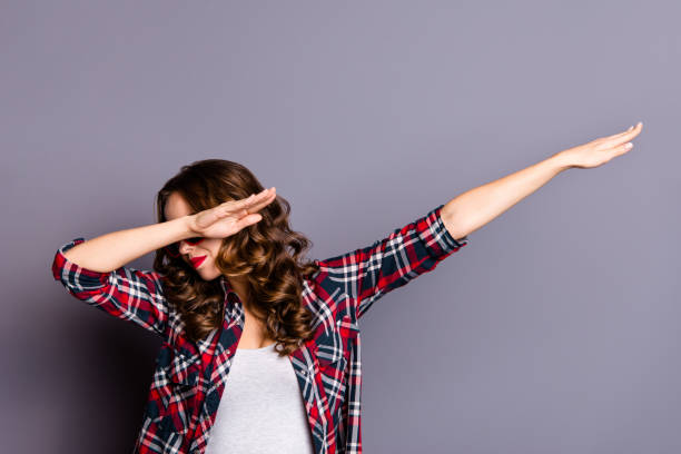 Close up portrait of beautiful amazing she her lady hands raised hide cover close hafl face strange dance moves red dark bright summer specs wearing casual checkered shirt isolated grey background stock photo