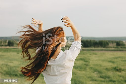 Close up portrait of beautiful long hair girl in white clothes in field, view from back. Sensitivity to nature concept