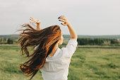 フィールドで白い服を着た美しい気楽な長髪の女の子の肖像画をクローズアップし、後ろから見ます。自然概念に対する感受性