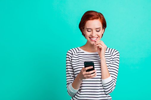 istock Close up portrait of beautiful cheerful foxy attractive she her lady with telephone in hand writing reading love letter from boyfriend wearing white striped pullover isolated on teal background 1097431694