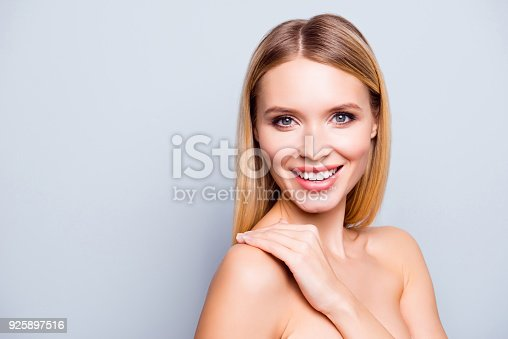 istock Close up portrait of beautiful lovely and smiling young woman with ideal skin and hair. She is touching her shoulder and enjoying the affect after cosmetological procedure. Isolated on grey background 925897516