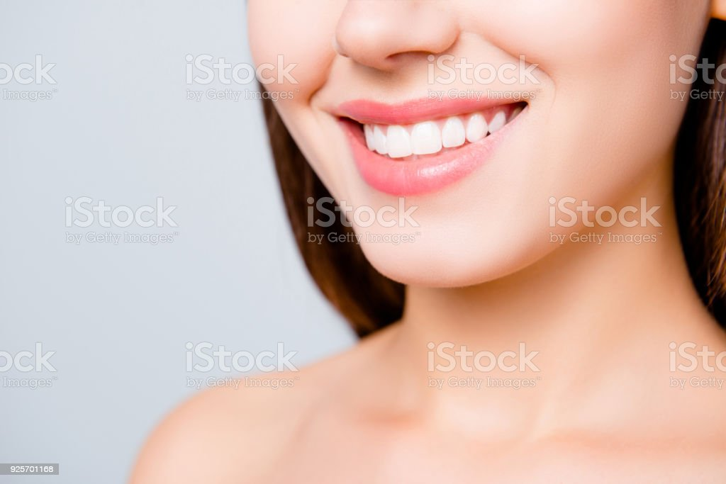 Close up portrait of beautiful wide smile with whitening teeth of young fresh woman isolated over white background, dental care stock photo