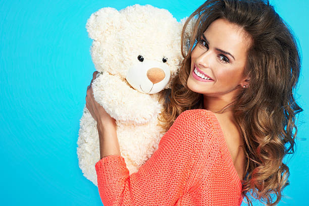 Close up portrait of beautiful woman holding teddy bear stock photo