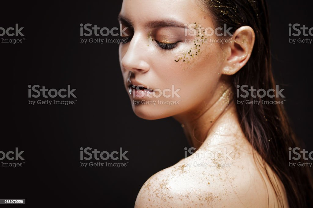 Close up portrait of beautiful woman with creative gold make up stock photo