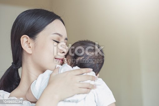 1049923194 istock photo Close up portrait of beautiful young asian mother kissing her newborn baby. 1049935234