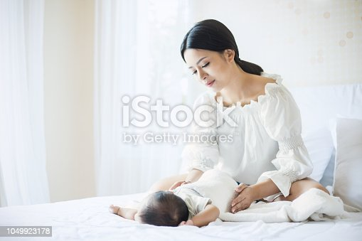 1049923194 istock photo Close up portrait of beautiful young asian mother with her newborn baby 1049923178