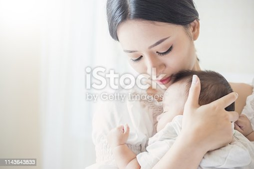 1049923194 istock photo Close up portrait of beautiful young asian mother with her newborn baby, copy space with bed in the hospital background. Healthcare and medical love, lifestyle mother's day concept 1143643833