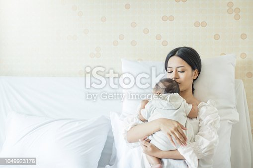 1049923194 istock photo Close up portrait of beautiful young asian mother with newborn baby 1049923176