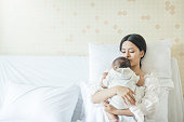 Close up portrait of beautiful young asian mother with newborn baby, copy space with bed in the hospital. Healthcare and medical love lifestyle mother'™s day concept