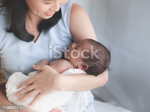 Close up portrait of beautiful young mother asian carrying little baby girl in home and sunlight in the morning. Healthcare, love, relationship concept