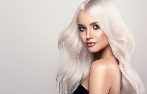 Portrait of beautifully looking young blonde haired woman, dressed in a bright evening makeup. Perfect model straightly gazing by kind, tender look at viewer.Coloration in blond. Stylish blond haire.