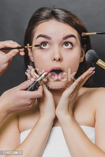 istock Close up portrait of beauty model girl and make up brushes, lipstick. Surprised facial expression. 1140226612