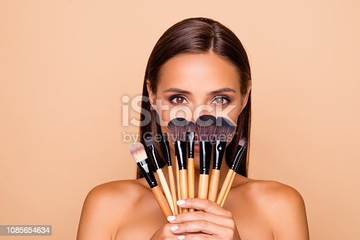 Close up portrait of brunette hair leisure lifestyle good-looking lovely pretty lady with her make up brushes shoulders she look at camera hide face isolated on pastel beige background
