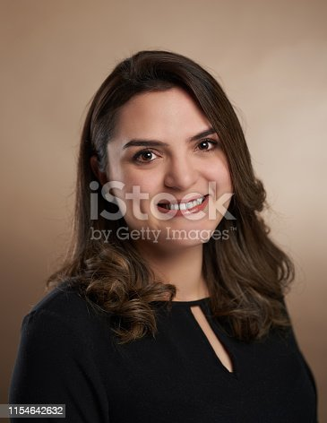 Close up portrait of brunette woman on brown studio background