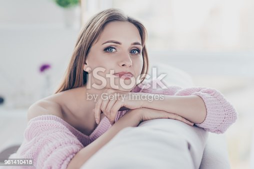 Close up portrait of calm relaxed charming beautiful gorgeous attractive in good mood pretty woman resting in house leaning on the back of divan wearing knitted warm jumper
