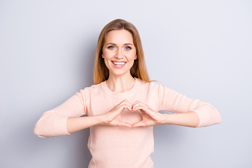 Close up portrait of charming lovely sweet sincere cute adorable pretty with toothy beaming smile woman making demonstrating heart on chest wearing casual light sweater isolated on gray background