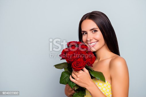 istock Close up portrait of cheerful attractive beautiful cute lovely woman with straight smooth hair wearing dotted yellow dress, cuddling roses to the face, isolated on grey background, copy space 924022332