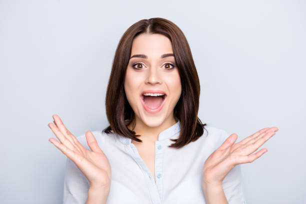 close up portrait of cheerful, charming, pretty, stylish woman with wide open mouth, short hair, holding palms near face, looking at camera, isolated on grey background - smile woman open mouth foto e immagini stock