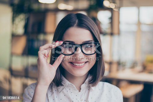 istock Close up portrait of cheerful smiling smart young pretty woman holding glasses in modern workspace 941838514