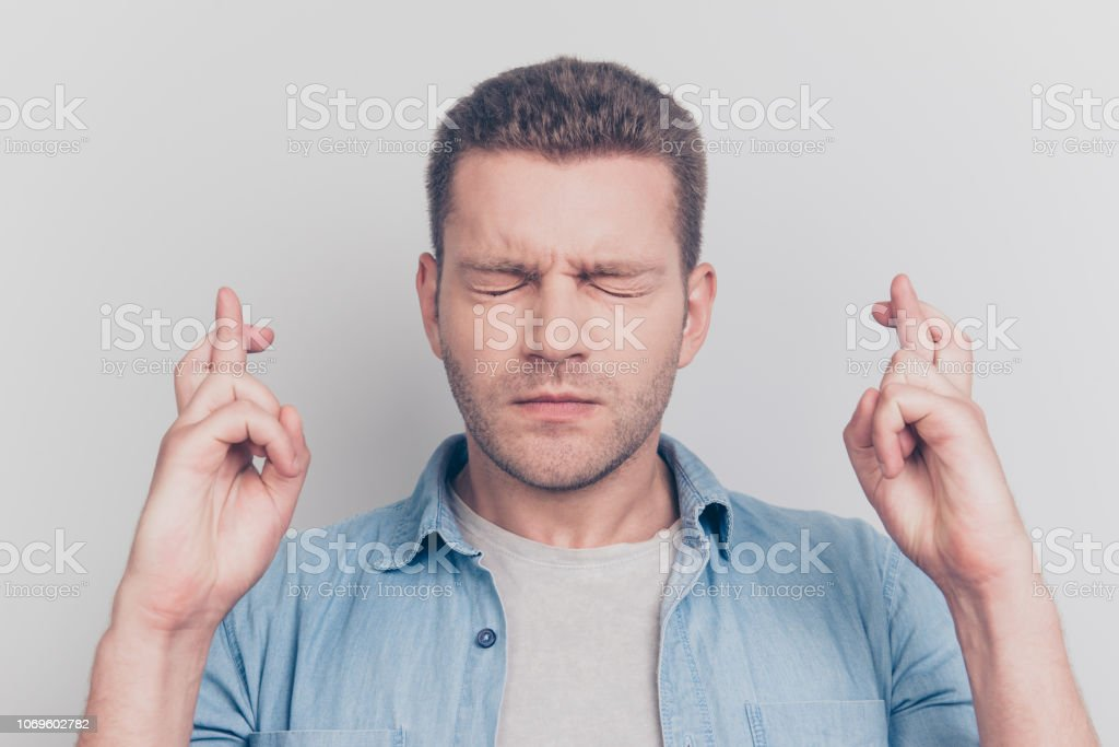Close up portrait of close eyes man cross fingers on two hands want plan best result for himself isolated on light gray background stock photo