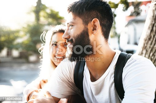 istock Close up portrait of confident bearded man looking away smiling while is embraced by his girlfriend which is looking at him outside while dating in the city. 1140404893