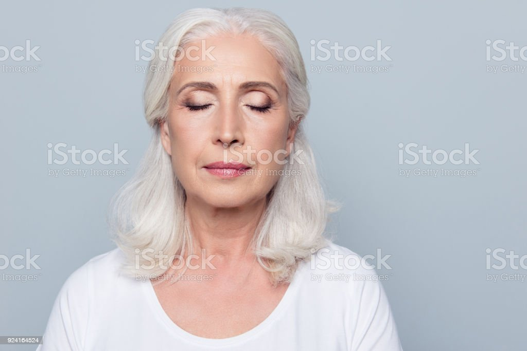 Close up portrait of confident concentrated mature woman with wrinkles on face, with closed eyes, with nude make up, isolated on gray background stock photo