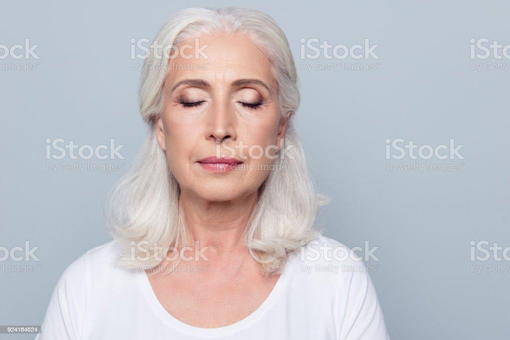 Nahaufnahme Portrait von zuversichtlich konzentrierte Reife Frau mit Falten im Gesicht, mit geschlossenen Augen, mit nude Make up, isolierten auf grauen Hintergrund – Foto