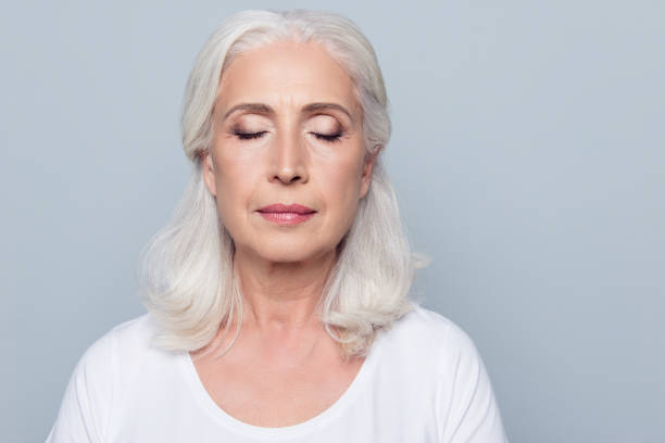 close up portrait of confident concentrated mature woman with wrinkles on face, with closed eyes, with nude make up, isolated on gray background - eyelid stock pictures, royalty-free photos & images