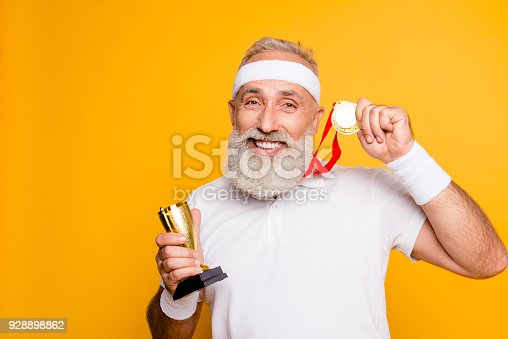 istock Close up portrait of crazy comic emotional cool grandpa holding precious reward. Body, health, care, lifestyle, game, challenge, champ, hero, leisure, training, workout, strength, power 928898862