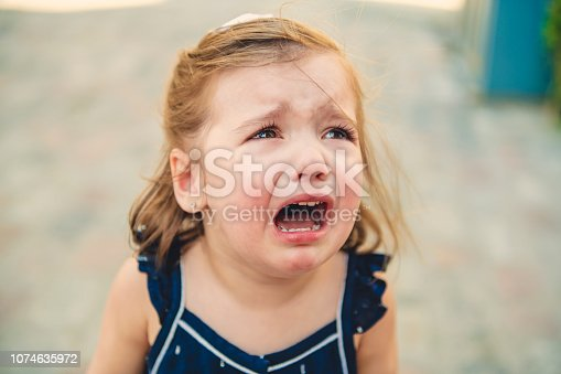 istock Close up portrait of crying little toddler girl with outdoors background. Child 1074635972