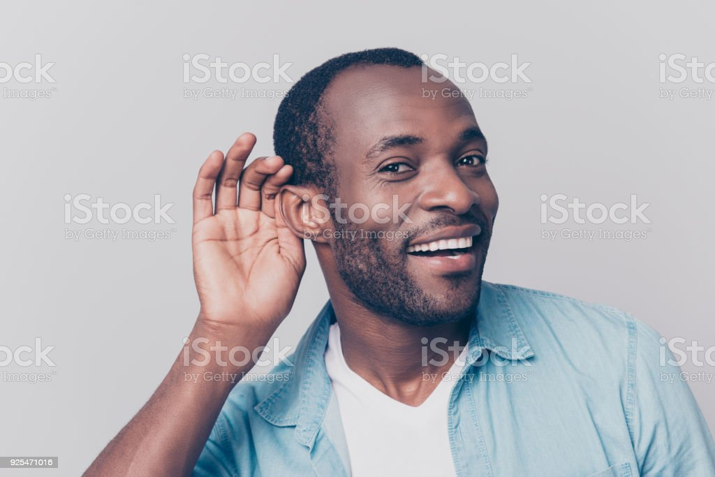 Close up portrait of curious interested delightful funny amazed cheerful surprised african man holding hand near ear and trying to hear the information isolated on gray background stock photo