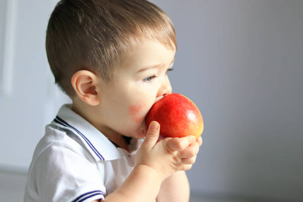 close up portrait of cute little baby boy with atopic dermatitis on his cheek holding and eating red apple. food allergy - allergie alimentari foto e immagini stock