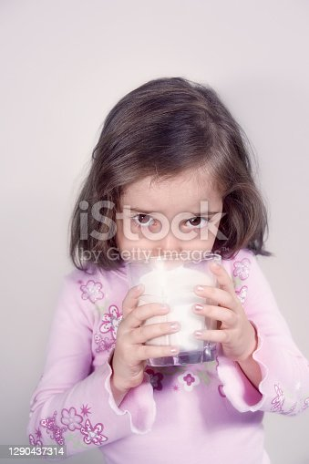 close up portrait of cute little girl drinking milk from a glass in domestic kitchen